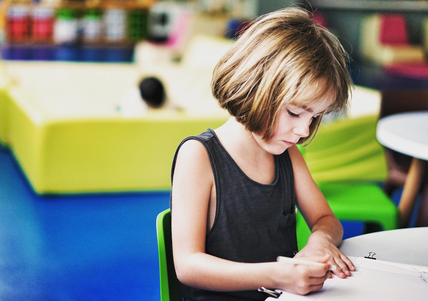 Girl seating on table writing on notebook